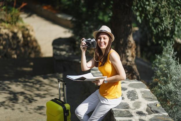 Laughing traveler tourist woman in hat with suitcase city map prendre une photo sur un appareil photo vintage rétro dans la ville en plein air. fille voyageant à l'étranger pour voyager en week-end. mode de vie de voyage touristique.