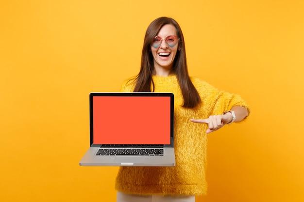 Laughing woman in heart verres pointant l'index sur ordinateur portable pc avec écran vide noir blanc isolé sur fond jaune vif. les gens émotions sincères, mode de vie. espace publicitaire.