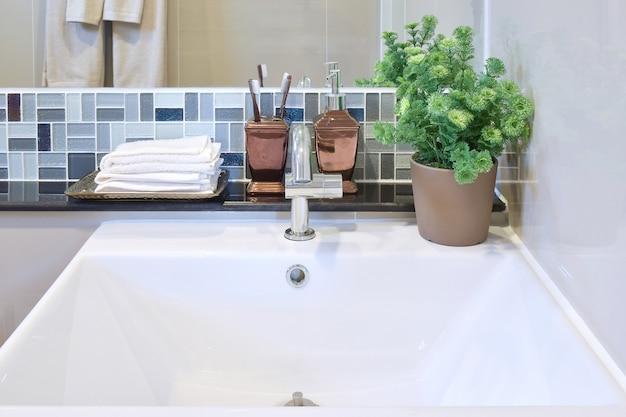 Lavabo et accessoires avec mur en mosaïque