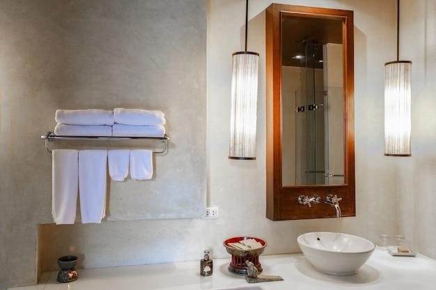 Lavabo en marbre moderne dans les toilettes ou la salle de bains d'un hôtel avec articles de toilette et serviettes propres
