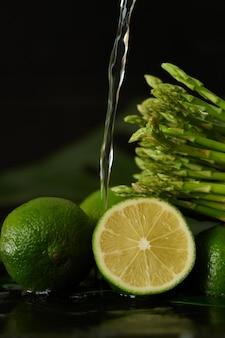Lavage de la chaux et des asperges avec un jet d'eau, verser de l'eau du robinet sur les légumes gros plan