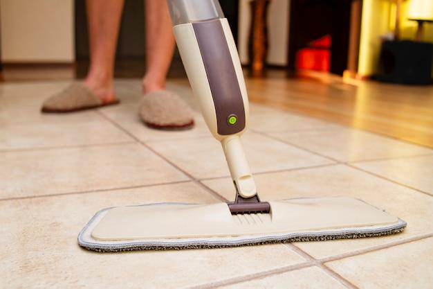 Lavage du sol avec une vadrouille à pulvériser le nettoyage de la maison est rapide et facile avec les services d'une entreprise de nettoyage