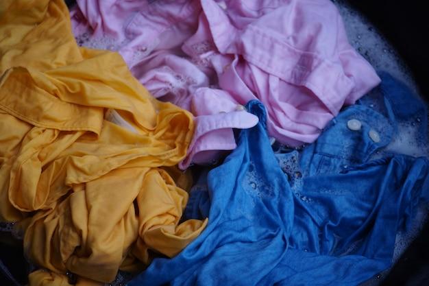 Lavage à la main chemise jaune, rose, bleue avec bassin en blanc bulles.