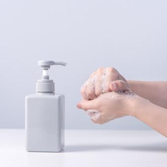 Lavage des mains. jeune femme asiatique utilisant du savon liquide pour se laver les mains, concept d'hygiène pour arrêter la propagation du coronavirus isolé sur fond blanc gris, gros plan.