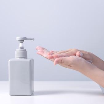 Lavage des mains. jeune femme asiatique utilisant du savon pour se laver les mains, concept d'hygiène pour arrêter la propagation du coronavirus isolé sur fond blanc gris, gros plan.
