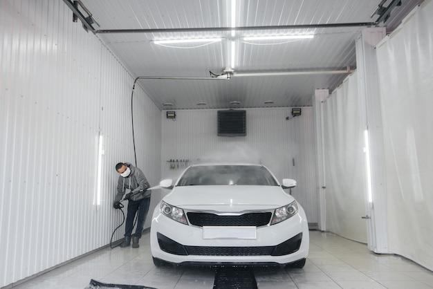 Lavage moderne avec mousse et eau haute pression de voiture blanche. lave-auto.