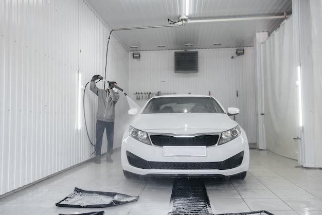Lavage moderne avec de la mousse et de l'eau à haute pression d'une voiture blanche. lave-auto.