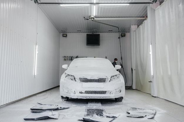 Lavage moderne avec mousse et eau haute pression de voiture blanche.