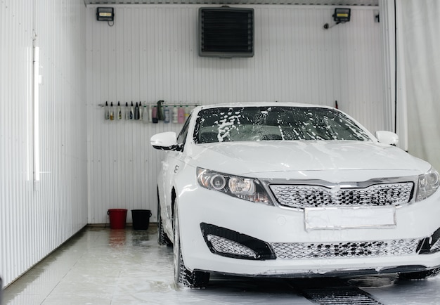 Lavage moderne avec de la mousse et de l'eau à haute pression d'une voiture blanche.
