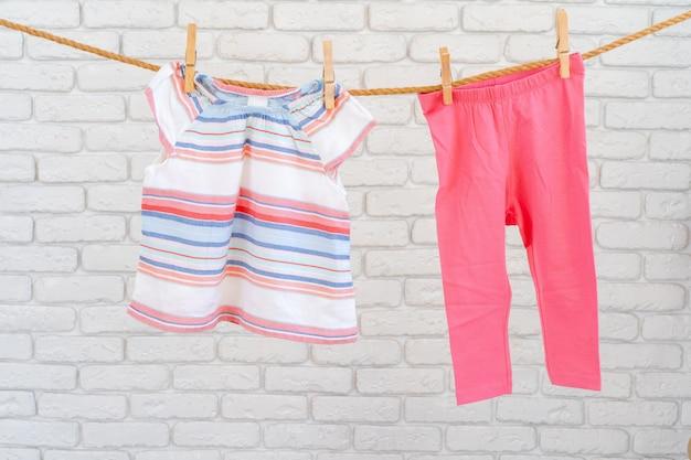 Lavage des vêtements de bébé épinglé sur une corde pour sécher