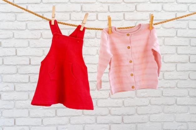 Lavage des vêtements de bébé épinglés sur une corde à sécher