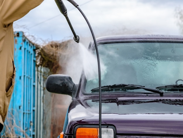 Lavage de voiture l'après-midi à l'extérieur avec un appareil à haute pression. un puissant jet d'eau éclabousse la saleté de la carrosserie violette de la voiture, du verre, des roues et des pneus.