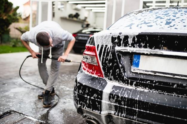 Lavage de voiture à l'eau sous pression, concept d'esthétique automobile (ou de voiturier).