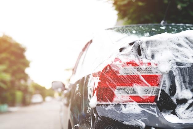 Lavage de voiture extérieur avec savon mousse actif. concept de service de lavage de nettoyage commercial.