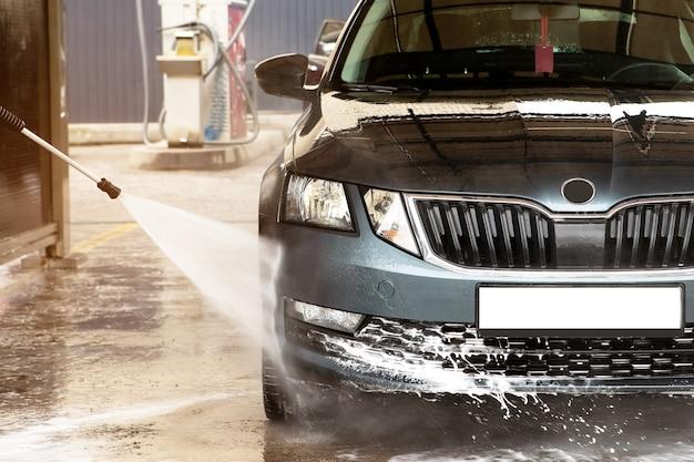 Lavage de voiture manuel avec de l'eau sous pression dans le lave-auto à l'extérieur.nettoyage de la voiture à l'eau à haute pression. lavage de voiture - avec un jet d'eau au service de lavage de voiture