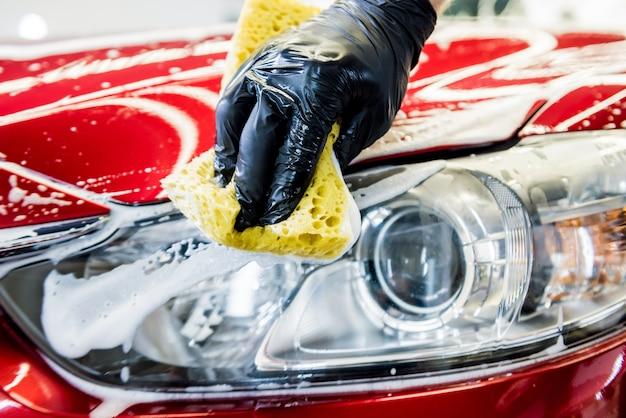 Lavage de voiture rouge avec une éponge sur un lave-auto