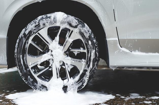 Lavage de voiture avec savon mousse actif. nettoyer le pneu de la roue. concept de service de nettoyage commercial.
