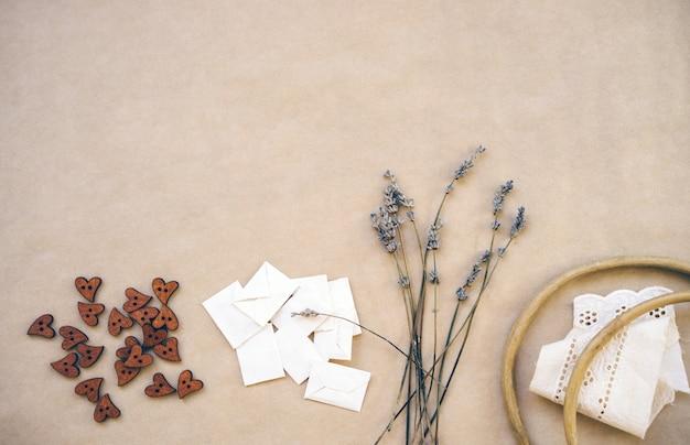 Lavande, boutons en bois, enveloppes faites maison, vieux cerceau en bois et rubans à ourlet sur papier kraft.