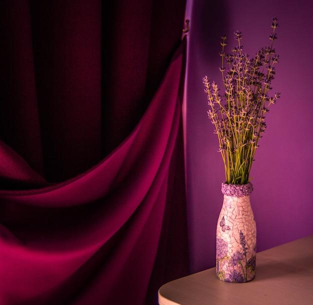 Lavande dans le vase sur la table. rideau violet et fond de mur violet.