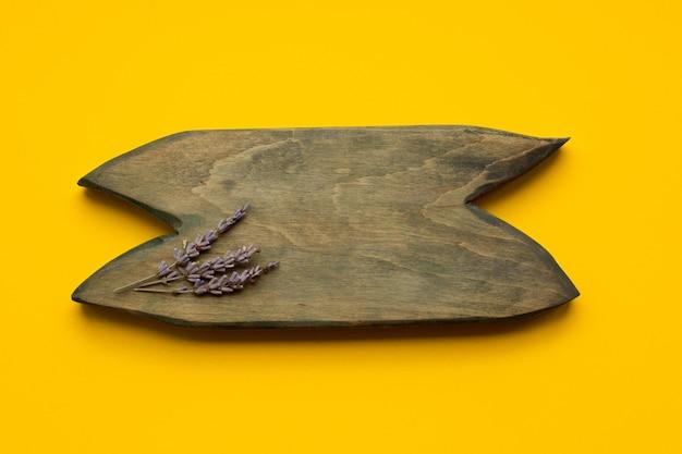 La lavande est joliment aménagée sur une planche de bois, vue de dessus, avec fond.