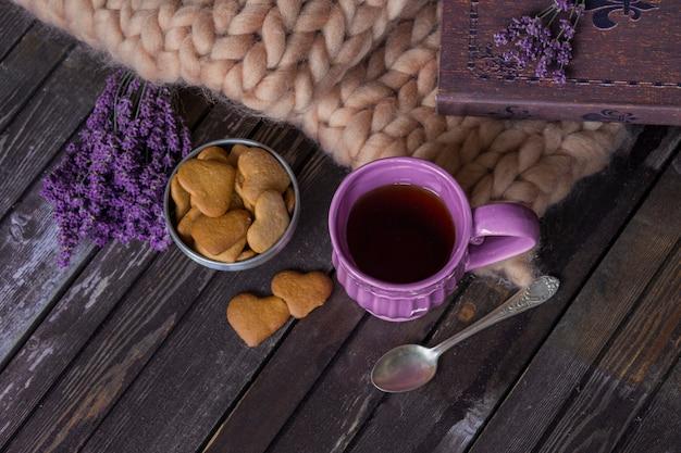 Lavande, plaid, livre, tasse de thé pourpre, guirlande et biscuits