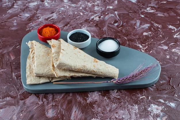 Lavash frais avec du sel et du poivre sur une planche.