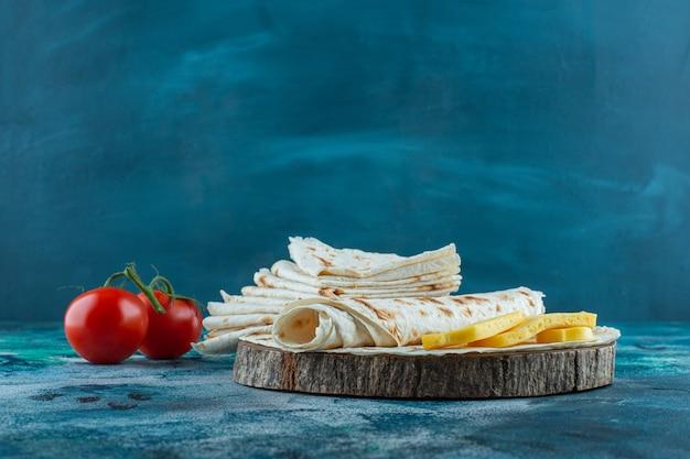 Lavash et fromage sur une planche à côté de tomates, sur le fond bleu.