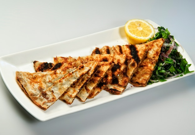Lavash grillé tranché sur plaque noire enveloppements de lavash de pain plat arménien sur fond de bois