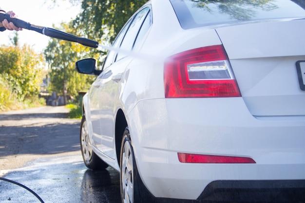 Lave-auto. lave-auto. l'homme lave la voiture. mousse