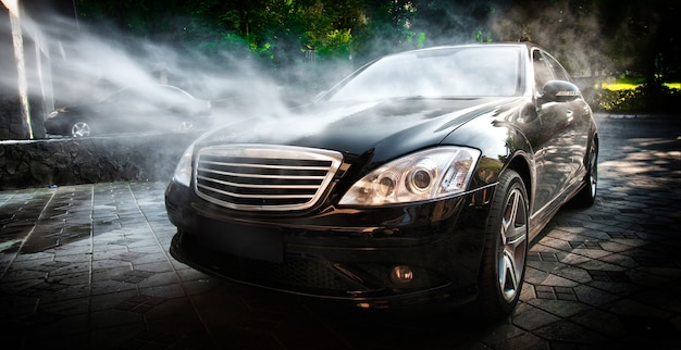 Lave-auto. nettoyage d'une voiture avec de l'eau à haute pression.