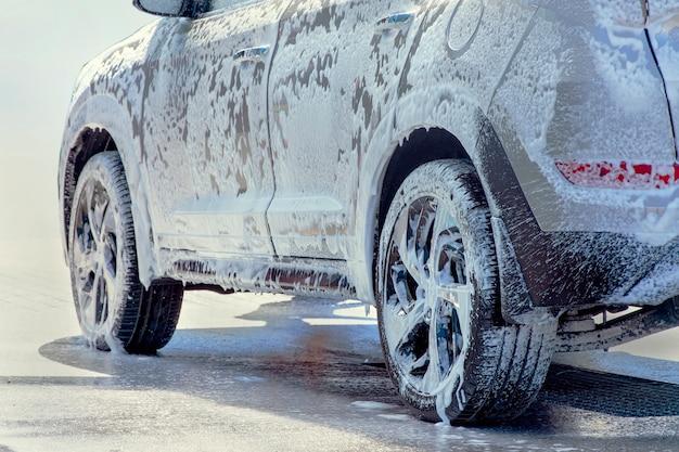 Lave-auto. la voiture en gros plan est dans la mousse active.