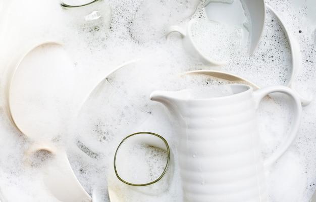 Lave-vaisselle, gros plan d'ustensiles trempant dans un évier de cuisine. vue de dessus