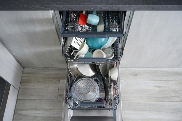 Lave-vaisselle, ouvert et chargé de vaisselle dans la cuisine, après lavage.