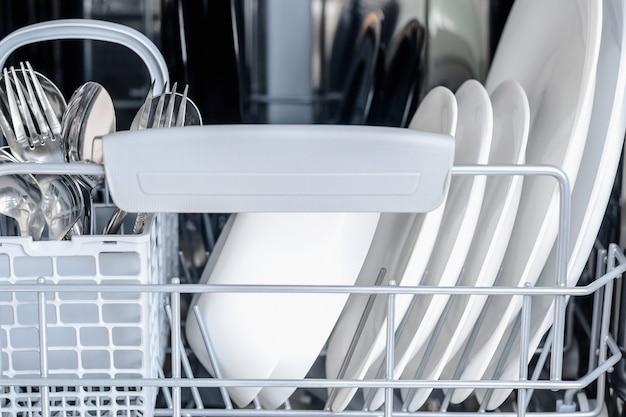 Lave-vaisselle ouvert avec verre propre et vaisselle.