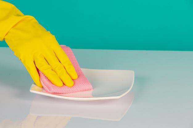Lave-vaisselle portant des gants jaunes sur un bleu.