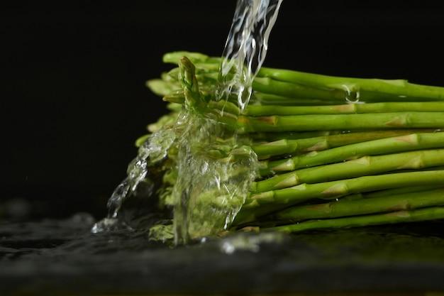 Laver les asperges avec un jet d'eau, verser de l'eau du robinet sur les légumes gros plan