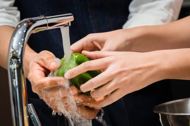 Laver le chili couple d'amoureux laver le piment dans la cuisine.