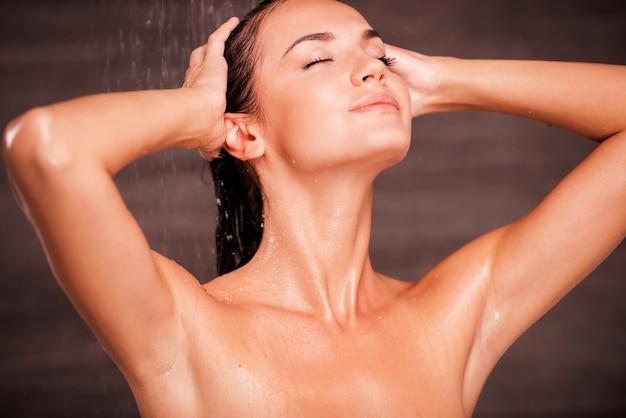 Laver ses problèmes. belle jeune femme torse nu debout dans la douche et se laver les cheveux