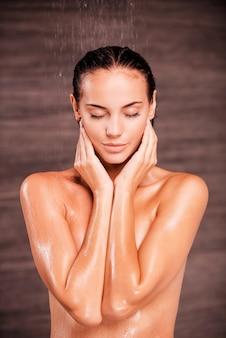 Laver le stress. belle jeune femme torse nu debout dans la douche et gardant les yeux fermés