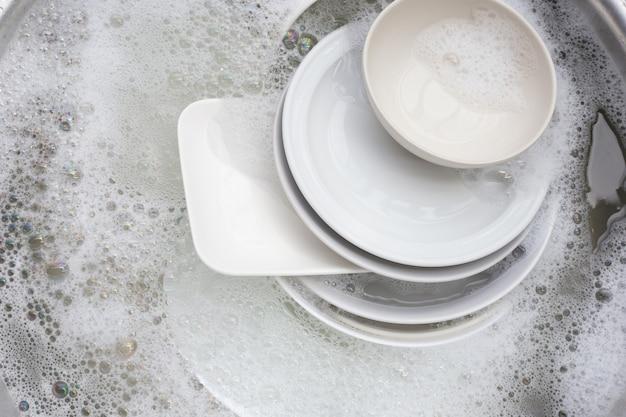 Laver la vaisselle, gros plan sur des ustensiles trempés dans un évier de cuisine.