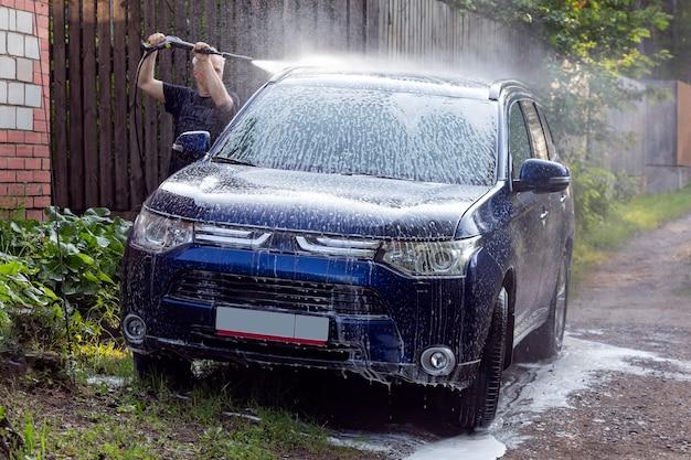 Laver la voiture avec du savon à l'aide d'un nettoyeur haute pression
