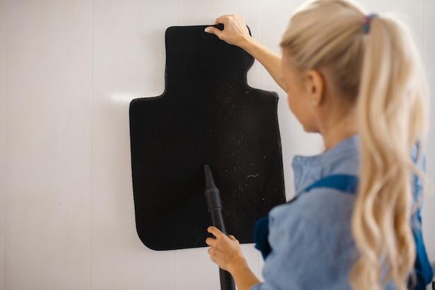 Laveuse avec aspirateur nettoie les tapis d'automobile, service de lavage de voiture. femme lave un véhicule, station de lavage de voiture, entreprise de lavage de voiture