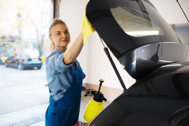 Laveuse femme essuie la cire en spray, service de lavage de voiture. femme lave un véhicule, station de lavage de voiture, entreprise de lavage de voiture
