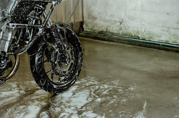 Lavez la moto à l'atelier de lavage de voiture. lave-auto en mousse sur roues