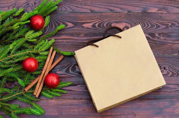 Lay plat d'un arbre de noël avec des boules rouges, des décorations et un sac en papier. vue de dessus