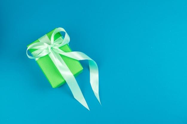Lay plat de boîte-cadeau décorée avec un arc sur fond bleu