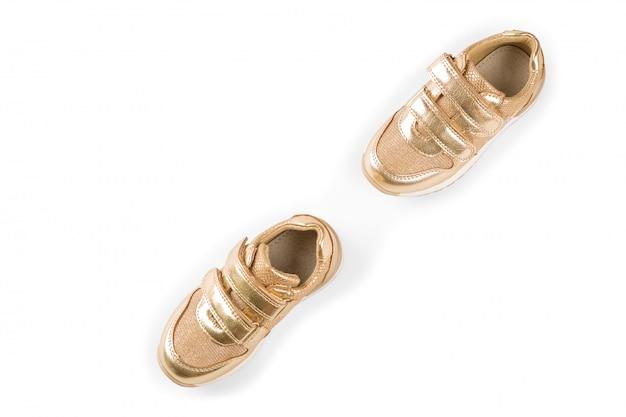 Lay plat. les chaussures de sport pour enfants d'or isolés on white