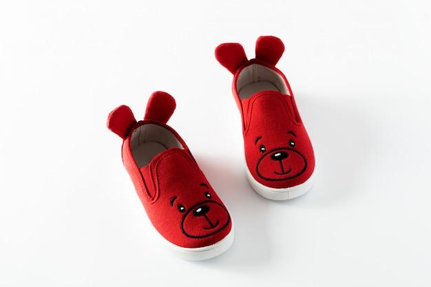 Lay plat. les chaussures de sport pour enfants rouges isolés sur fond blanc