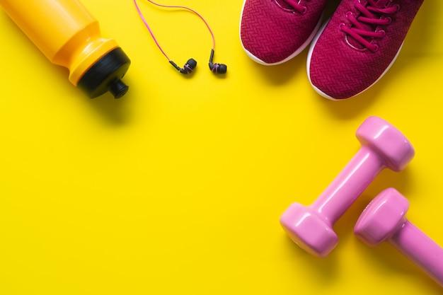 Lay plat de chaussures de sport rouges, des haltères roses, des écouteurs, une bouteille d'eau sur backgro jaune