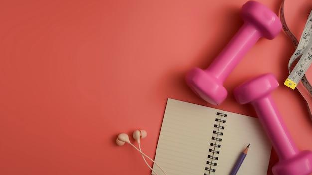 Lay plat de crayon de bloc-notes haltères équipement de fitness et des écouteurs sur fond rose